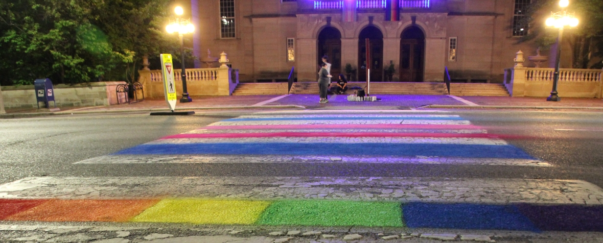 Photo: Night view of Arlington, MA Town Hall decorated for Pride 2019. Rainbow and trans flags hang from the building and the crosswalk is painted with rainbow and trans flag colors (blue, pink, white, pink, blue). People and spray paint cans are in the background.